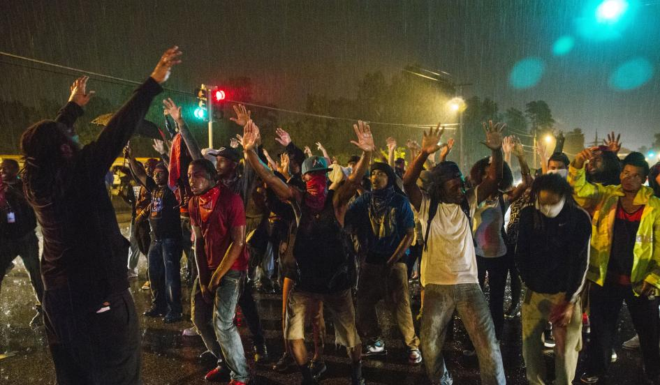 Protesters stand in a street in defiance of a midnight curfew meant to stem ongoing demonstrations in reaction to the shooting of Michael Brown in Ferguson, Missouri August 17, 2014. REUTERS/LUCAS JACKSON